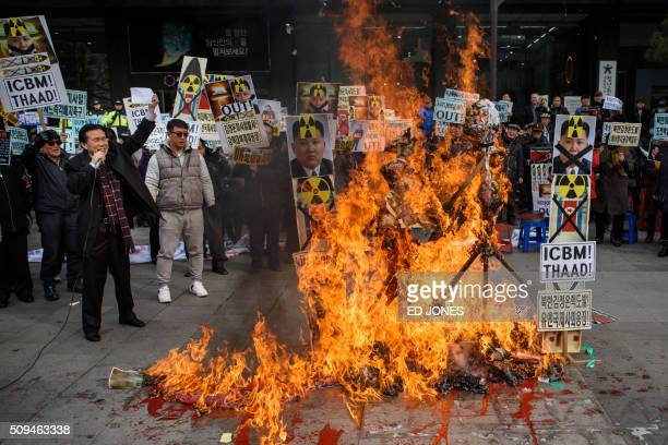 TOPSHOT AntiNorth Korean activists burn placards showing North Korean leader Kim JongUn as they protest the latest nuclear test and rocket launch by...