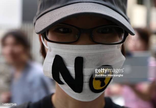 Antinuclear activist wears the mask attend the protest against to restarting the commercial nuclear reactors on July 27 2012 in Osaka Japan Two of...