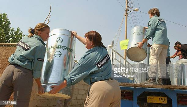 Antinuclear activists from Greenpeace unload new barrels from a truck during a campaign to replace barrels contaminated with radioactive yellowcake...