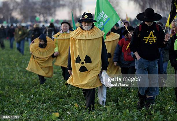 Antinuclear activists march through a field after a demonstration against the ongoing nuclear waste convoy to the storage facility in a salt deposit...