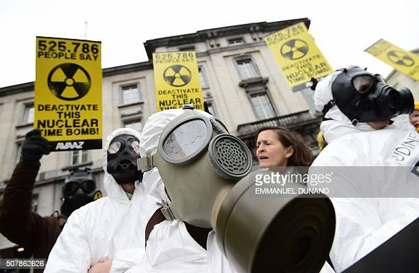 Anti-nuclear activists wearing gas masks and holding up placards reading '525 786 people say - Deactivate this nuclear time bomb! stage a protest...