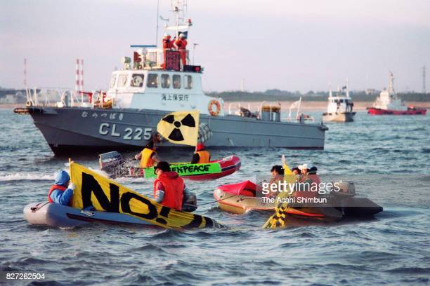 Antinuclear protesters on rubber boats are blocked by a Japan Coast Guard vessel as plutonium carrying vessel 'Akatsuki' cruises toward Tokai village...