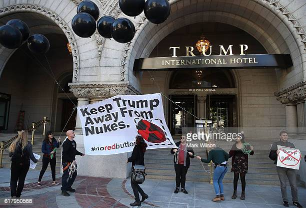 Antinuclear weapon activists raise a banner that reads Keep Trump Away From Nukes during a rally outside the Trump Hotel in Washington DC The...