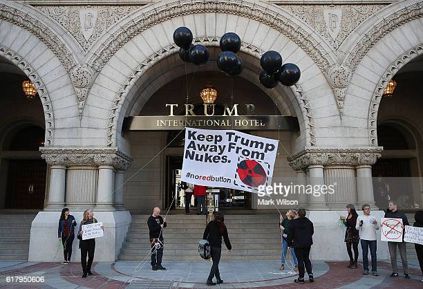 Antinuclear weapon activists raise a banner that reads Keep Trump Away From Nukes during a rally outside the Trump International Hotel in Washington...