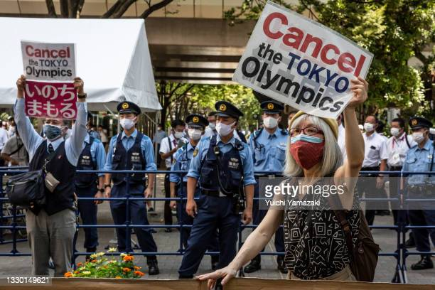 Anti-Olympics protesters demonstrate during the Olympic Torch Relay Celebration event on July 23, 2021 in Tokyo, Japan. Protesters gathered to...