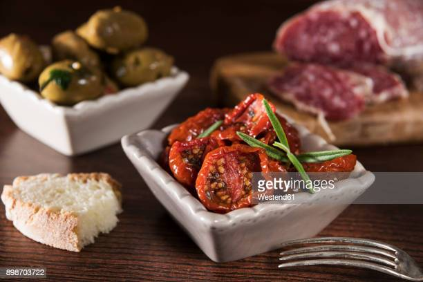 antipasti, pickled olives, pickled tried tomato, olive bread, salami - antipasto stock photos and pictures