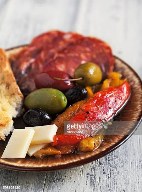 antipasto with fire roasted red and yellow peppers, mixed olives, provolone cheese, sopressata and italian bread - olive pimento stock photos and pictures