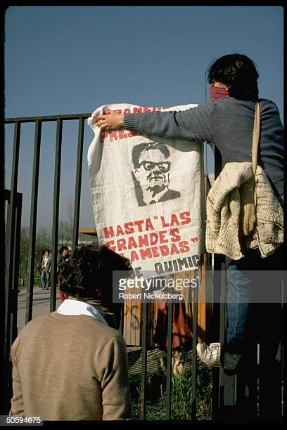 Anti-Pinochet govt. Students hanging wanted poster on fence during student protests at Catholic Univ. & in downtown area.