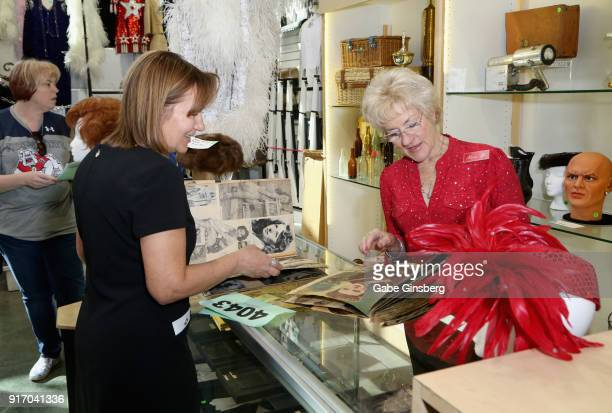 Antique appraiser Carole Molchany and Nora Hughes both of Nevada look through scrapbooks once owned by Debbie Reynolds during an auction of Debbie...
