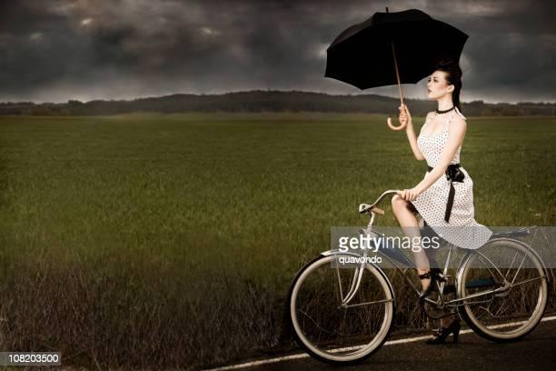Alte Fahrrad mit schöne Brunette Junge Frau in stürmischen Wetterbedingungen