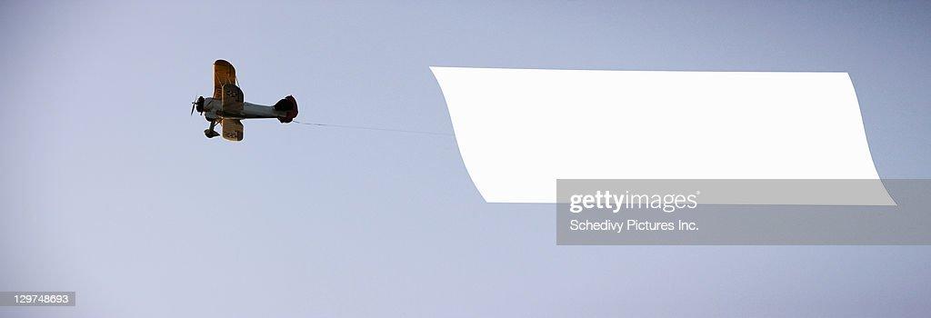 Antique biplane tows blank banner : Stockfoto