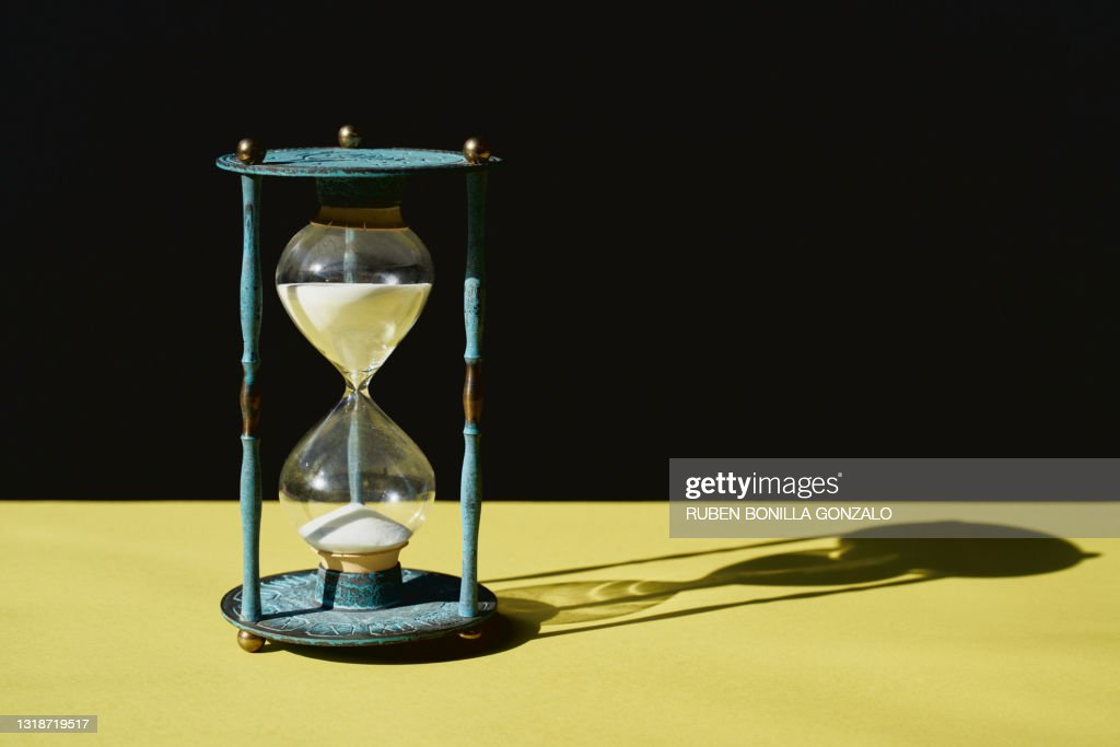 Antique Blue Hourglass time with sand running through against black and yellow background : Stock Photo
