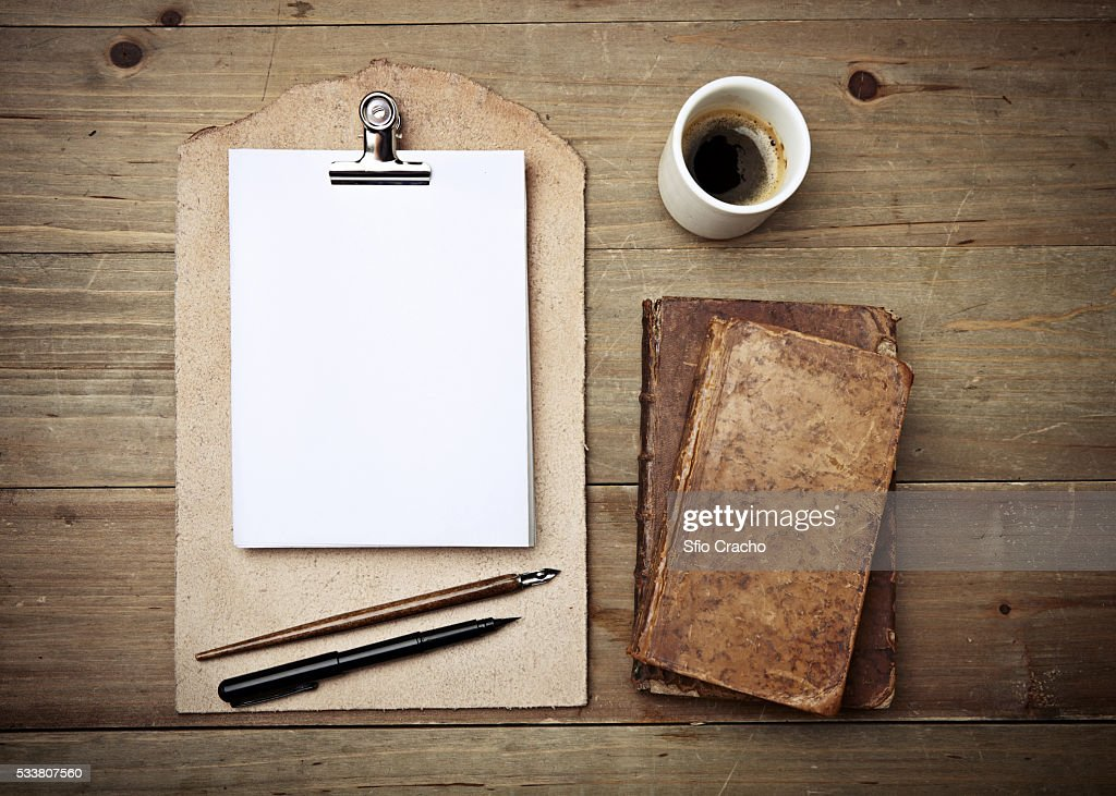 Antique books, cup of coffee and leather clipboard : Foto stock