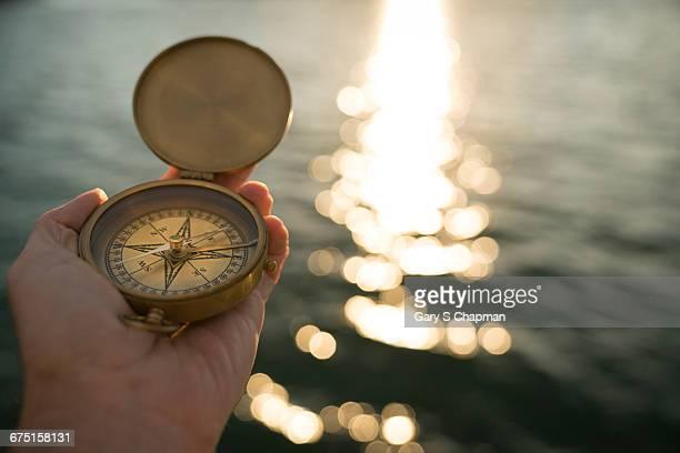 Antique brass compass over ocean at sunset