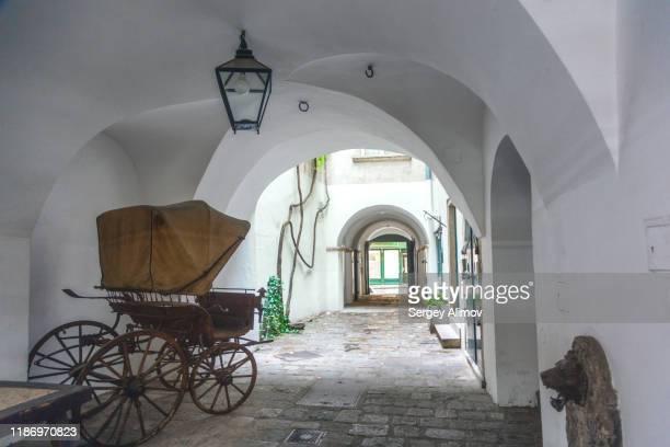 antique carriage in arch-shaped yard of vienna - distrito histórico fotografías e imágenes de stock