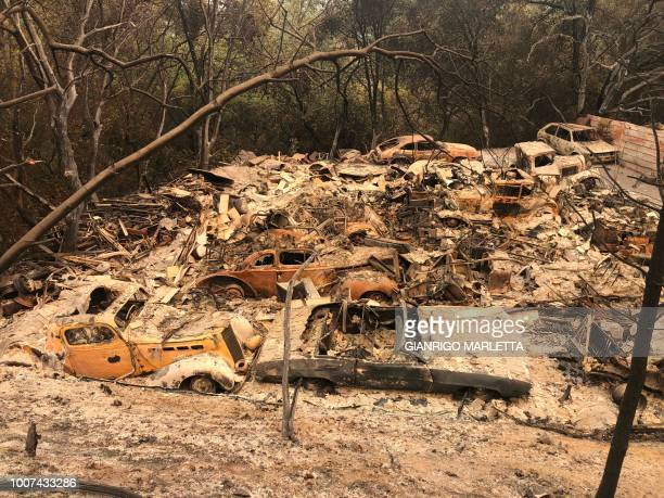 TOPSHOT Antique cars part of a collection lie in rubble in a devastated neighborhood July 29 2018 near Redding California where firefighters say only...