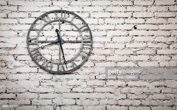 Antique Clock Mounted On Brick Wall