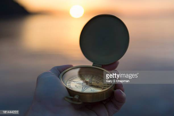 Antique compass and sunrise over water