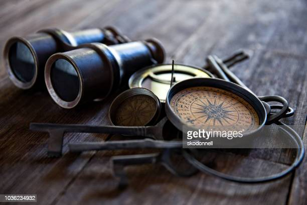 antique compasses keys and binoculars on old wood - binoculars stock pictures, royalty-free photos & images