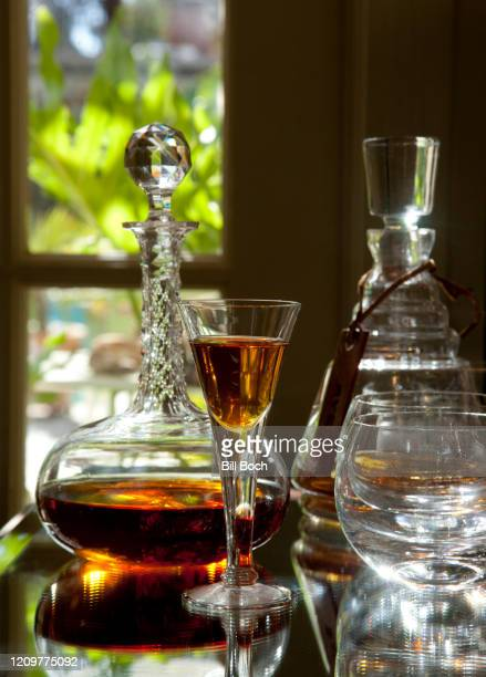 antique crystal glass of brandy or port wine and a crystal decanter behind it in a elegant home bar or drink establishment—part of a series - bar drink establishment stock pictures, royalty-free photos & images