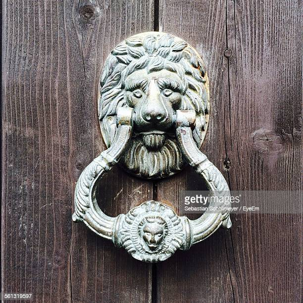 antique door knocker on wooden door - door knocker stock photos and pictures