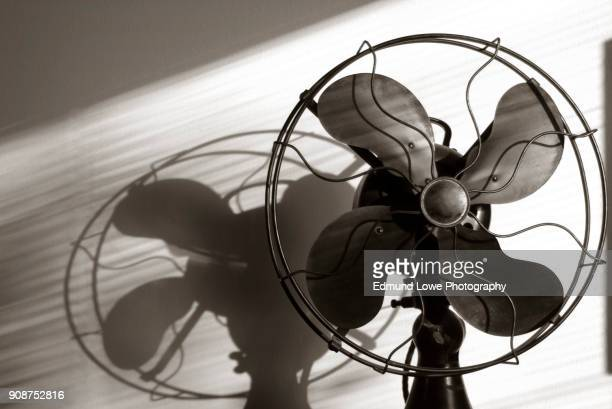Antique Fan With Light Streaming Through the Window Blinds.