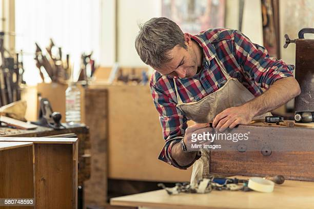 Antique furniture restorer using a pencil drawing and planning his work.