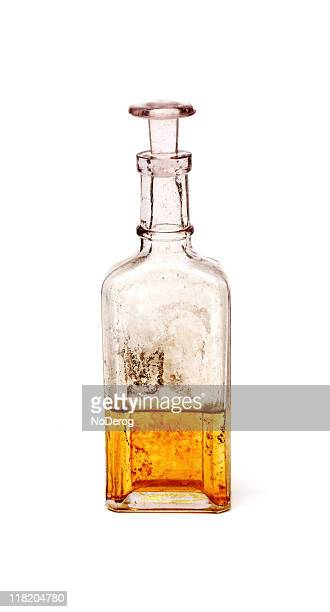 antique glass bottle containing golden liquid - potion stock photos and pictures