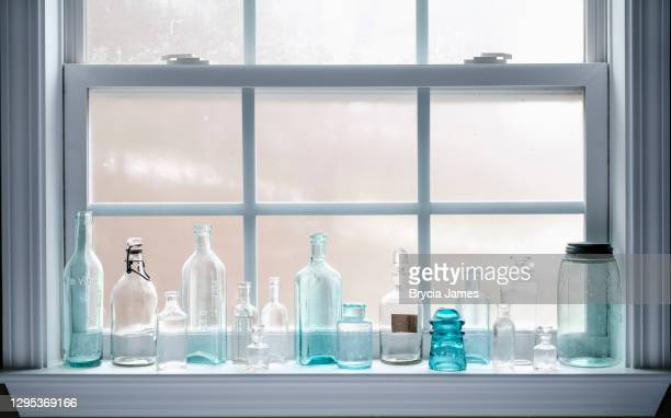 antique glass bottles on a windowsill - brycia james stock pictures, royalty-free photos & images