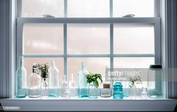 antique glass bottles on windowsill - brycia james stock pictures, royalty-free photos & images