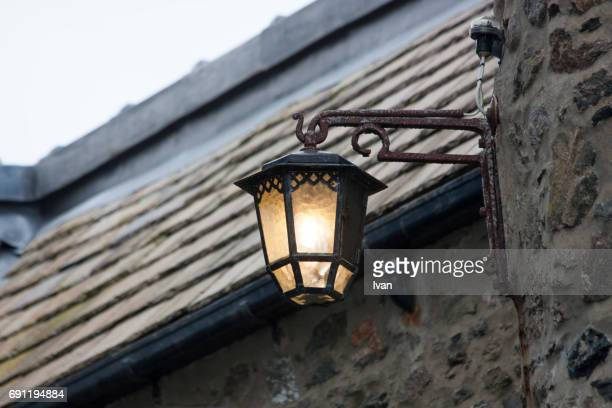 Antique Lighting Fixture Against Old Stone House