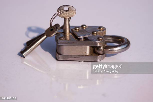 antique lock and key placed on reflective surface - リフレクター ストックフォトと画像