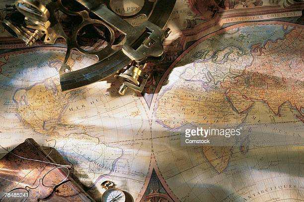 Antique navigation tools and glasses on top of world map