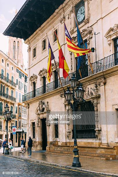Antique ornate town hall of Palma de Mallorca with the national flags