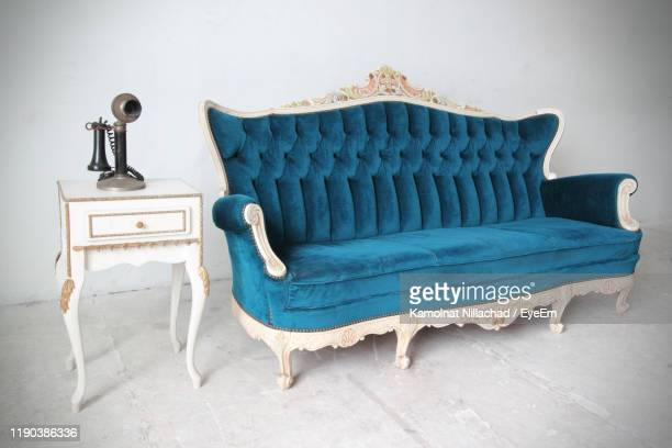 antique phone on table by vintage sofa against wall at home - candlestick phone stock pictures, royalty-free photos & images