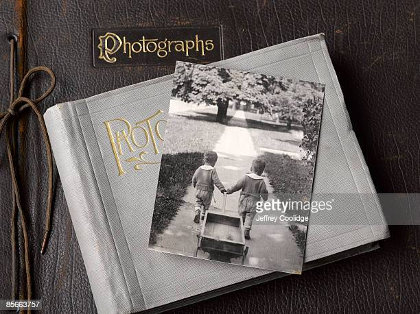 antique photo of young boys pulling wagon - childhood photo album stock photos and pictures