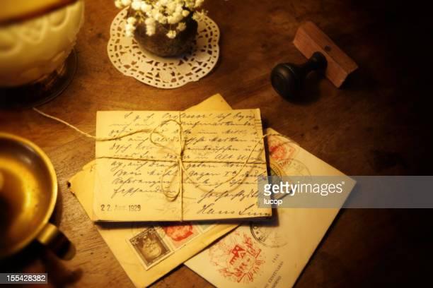 Des cartes postales anciennes et courrier enveloppe sur un bureau en bois