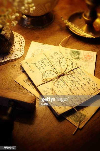 Antique postcards and mail envelops on a wooden desk