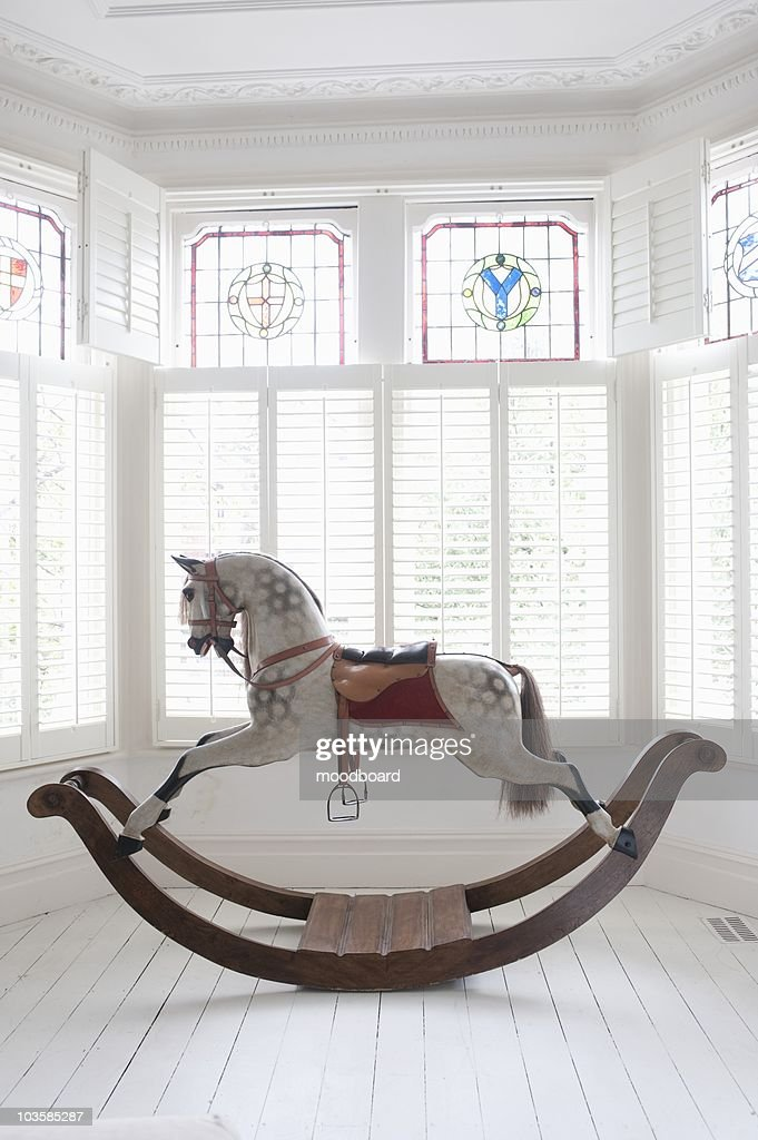 Antique rocking horse in bay window with stained glass,  London : Stock Photo