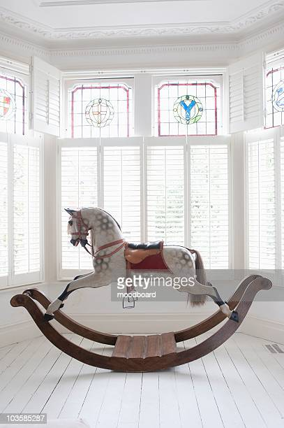 antique rocking horse in bay window with stained glass,  london - floorboard stock photos and pictures