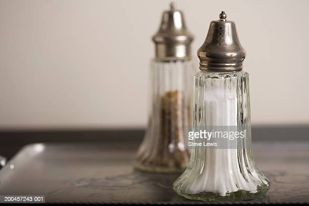 Antique salt and pepper shakers on tray, close-up