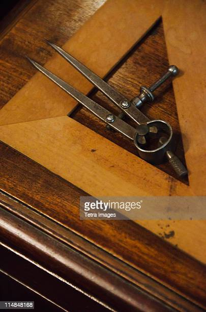 Antique set square and pair of compasses on wooden table