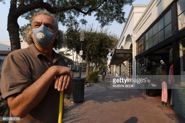 Antique shop owner Alan Howard takes a break from sweeping up ash in front of his store on State Street the main shopping street in Santa Barbara...