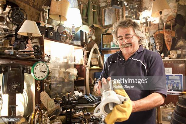 antique store owner polishing old coffee maker - antique shop stock pictures, royalty-free photos & images