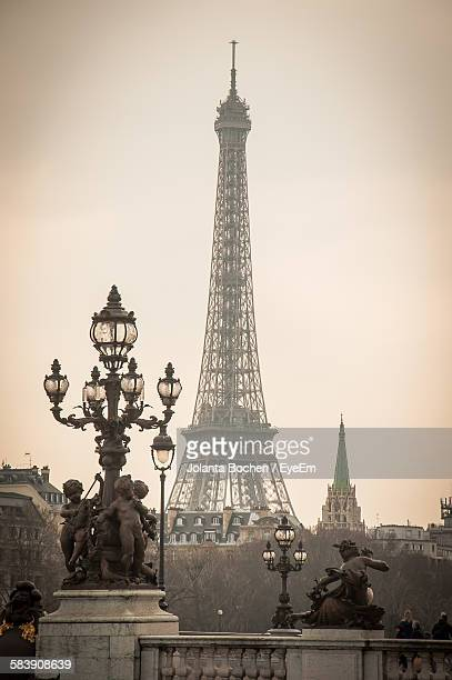 Antique Street Light With Statue In Front Of Eiffel Tower Against Sky