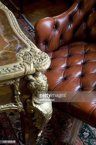 Antique Table and Chesterfield Leather Armchair with Oriental Rug
