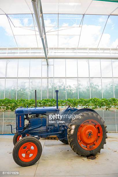 Antique tractor inside a greenhouse with strawberry plant in hydroponics farm in Ticino, Switzerland.