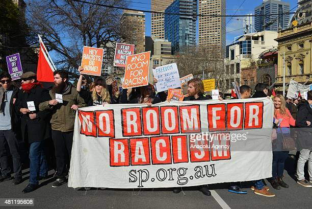 Antiracism activists hold placards as antiIslam protesters stage rally in Melbourne Australia on July 18 2015 Hundreds of police were deployed in...