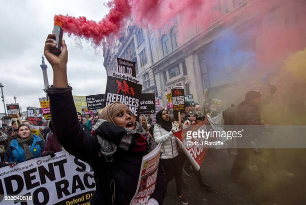 Antiracism demostrators let off flares during a march against racism on March 17 2018 in London England The march is organised by the group Stand Up...