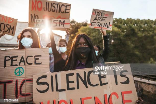 コヴィッド-19パンデミックスプレッドを保護するためにフェイスファスクで反人種差別抗議 - 社会運動 ストックフォトと画像